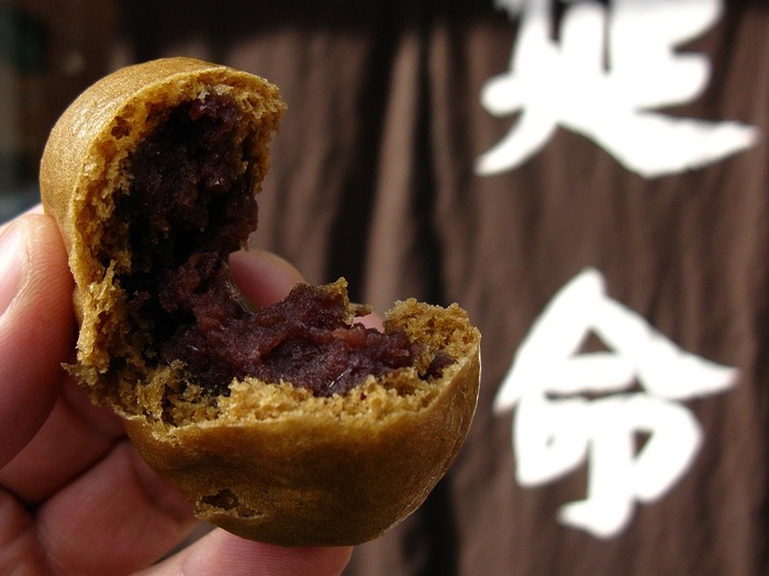 """「延命堂」は日本で初めて""""温泉饅頭""""を作ったと云われる熱海の有名な老舗和菓子店です。 看板商品『延命饅頭』は、「湯前神社」傍に元々店を構えていた店主が、自噴する温泉蒸気を見て饅頭を蒸し上げることを思いついて商品化した名物です。"""