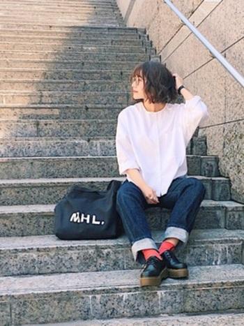 白いシャツにデニムというベーシックなスタイルなのに、ひとつひとつのアイテムが洗練されているので、シンプルな上品さが感じられます。厚底の靴と赤い靴下にぱっと目が惹かれます。