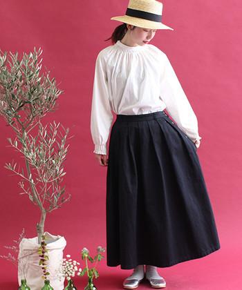 白ブラウスに、黒のフレアスカートを合わせたコーデ。スタンド襟のブラウスは、見える肌の面積が少ないため上品見えしやすいアイテムです。モノクロでまとめた着こなしは、ハットなどの小物で味付けするとおしゃれな雰囲気に仕上がります。