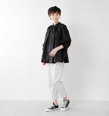 黒のブラウスに白のパンツを合わせた、モノトーンコーデ。靴や帽子などの小物も白黒でまとめて、上品なスタイリングに。足元のスニーカーでちょっぴりカジュアルダウンしているのもポイントですね。