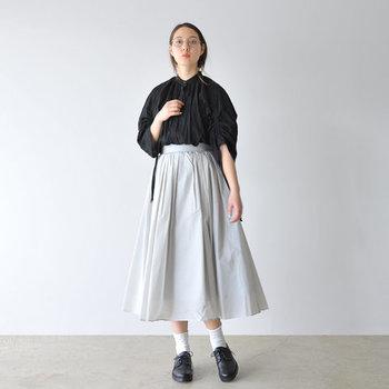 ゆったり着られる黒のブラウスを、フレアスカートにインしたスタイリング。たっぷりと余裕を持ったブラウジングで、体型をカバーしつつ女性らしい着こなしに仕上げています。