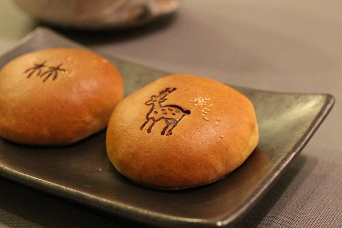 """この可愛らしい""""鹿""""と""""林""""の焼印が入った「奈良饅頭」がマストです! """"鹿""""は、氷砂糖でじっくり炊いた白餡。""""林""""は、上白糖に黒糖をブレンドして炊いた黒餡です。どちらも、しっとりとした生地が餡を包んでいて美味。"""