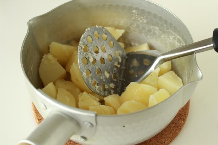 お湯を切ったら、もう一度火にかけ、粉ふきいものようになるまで水気を飛ばします。その後、熱いうちにバターを加えて、マッシャーなどでつぶします。