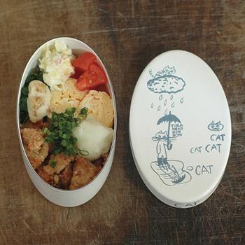 """【倉敷意匠のほうろうお弁当箱】 こちらは先ほどパステルカラーのお弁当箱コーナーで紹介した倉敷意匠さんのお弁当箱。かわいい猫の絵は、""""旅するレストラン""""の「トラネコボンボン」。主宰する中西なちおさんのブログにも登場するこの猫は、世界観とあわせて多くのファンを集めています。"""