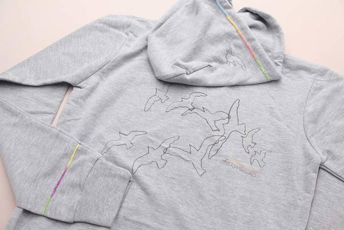 バックプリントのかもめの群れからは1羽がフードに飛び出し、遊び心溢れるお洒落なデザインが目を引きます。段染めの刺し子糸は使用部分によって色がグラデーションになり、一つとして同じ色合いのものがありません。1点ごと、ひと針ごとの個性を楽しむことができるのも、「大槌復興かもめパーカー」ならではの魅力です。