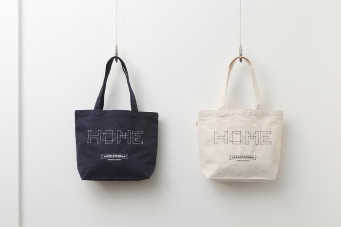 こちらはナチュラルなキャンバス地に、モダンな刺し子柄が映えるおしゃれなトートバッグ。バッグのデザインを手掛けたのは、人気アーティストのCDジャケットやBEAMSのTシャツのデザインなど、多岐にわたり活躍するアートディレクター/デザイナーの榊原直樹氏。ロゴタイプの「HOME」には、故郷や家など、誰もが大切にしているもの、大切にしたくなるもの、という想いが込められています。