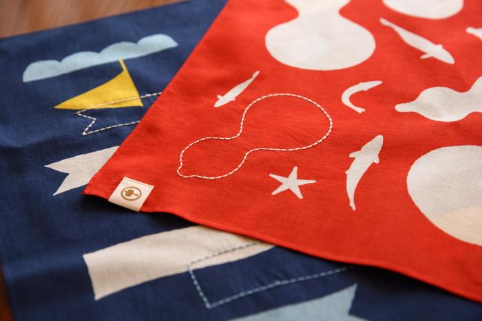 ひょうたんの形をした蓬莱島は「ひょっこりひょうたん島」のモデルになったとも言われ、大槌町の人々が愛してやまない町のシンボルです。マリン調のデザインがおしゃれな「大漁旗」も、蓬莱島をモチーフにした「ひょうたん島」も、どちらも鮮やかな布地に一針一針施した刺し子が美しく映えます。ポップなデザインと手縫いのステッチが可愛いマルチクロスは、ご家族やお友達へのプレゼントにもおすすめです。