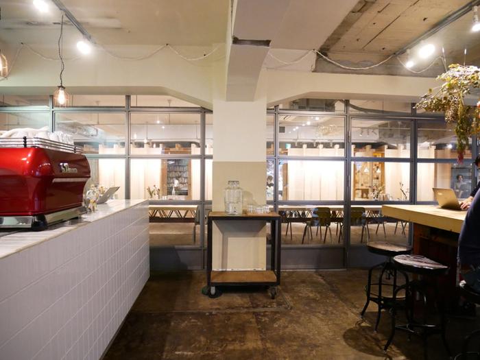 中に入ると、大きなテーブルに8席、外には木製のベンチが… テーブルの脚が廃材で作られていたり、配送センター時代のベルトコンベヤーがそのまま残されていたりと、所々に遊び心が感じられる空間に。 ガラスの向こう側の小部屋は、それぞれ小さなオフィスになっていて、カフェスペース側からはミーティングルームなども見えるそうです。