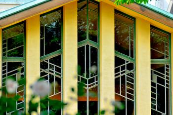 中央棟を中心に、左右に東教室棟・西教室棟を配置。完全にシンメトリーになるようなデザインがとても洒落ています。ホールの大きな窓は、明日館の顔とも言えるシンボリックな部分です。幾何学的な模様を木の枠だけで表現した窓枠や桟は、デザイン的に優れているだけでなく、特別な材料を必要としないので工費を低く抑えることができ、ライトの工夫が表れています。