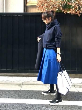 ネイビーのパーカーとブルーのフレアースカートを合わせた同系色コーデ。落ち着いたトーンの中に、鮮やかなブルーカラーが印象的です。パーカーの袖をロールアップしてこなれ感を演出して。
