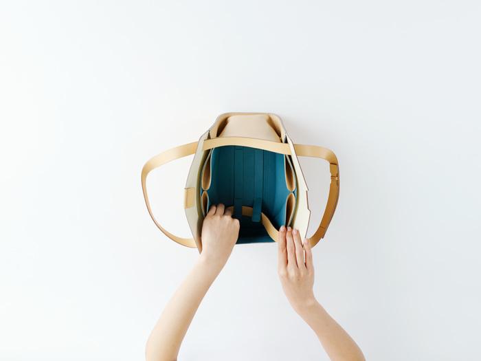 「Flat bag」は形を変えられるだけではなく、ベルトの長さを調節することによって、ショルダーバッグ・トートバッグ・ハンドバッグの3通りの使い方ができます。片側のベルトを引くとショルダーバッグ、両側のハンドルを引くとトートバッグに、さらに写真のように底のベルトとホックでショルダーを留めるとハンドバッグに。シーンやコーディネートに合わせて自在にアレンジできる「Flat bag」なら、自由に、自分らしいお洒落が楽しめそうですね。