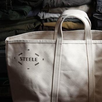シンプルでざっくりとした作りでありながら強固なつくりが魅力的な「STEELE CANVAS」 のトートバック。肉厚なキャンバス地に、さりげなく入ったステンシルのロゴマークがとってもお洒落です。 スーパーへのお買い物は勿論、あれこれ詰め込んでお出かけしたい人にはたまらないサイズ感です。とっても丈夫な作りなので、普段使いにも、ハードユースにも、肩肘張らず様々なシーンで活躍してくれることでしょう。また、使うほどに味わい深く、より愛着が沸く、パートナー的存在に!