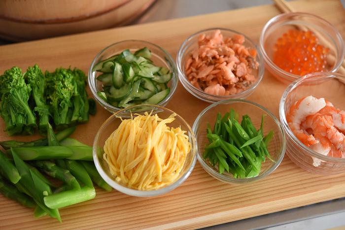 用意する具材は大きく分けて3種類。 「①食感のよい青みのある野菜」――菜の花やアスパラ、絹さや、きゅうりなど 「②塩気のある魚介類」――イクラ、鮭、えびなど 「②色味のよい錦糸卵」 この3種を組み合わせられるように準備するのがポイントです。今回冨田さんが用意したのは「ゆでた菜の花、ゆでたアスパラ、ゆでた絹さや、木の芽、きゅうりの塩もみ、イクラの醤油漬け、ゆでたえび、鮭フレーク、錦糸卵」の全9点。すべてを用意する必要はないので、3種類のバランスだけは意識するようにしましょう。