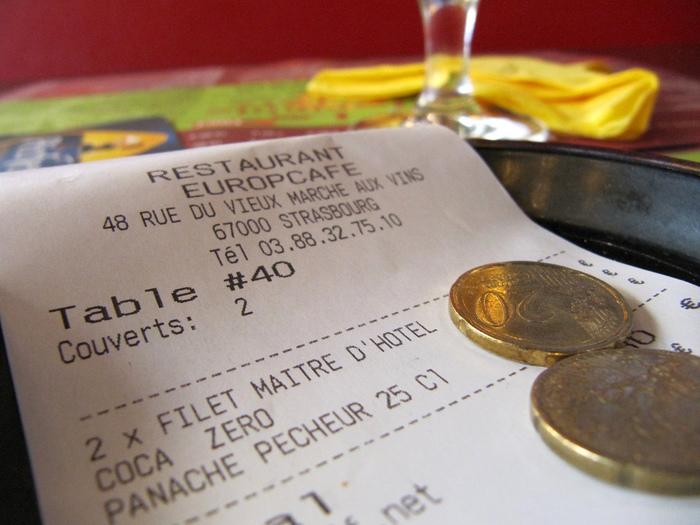 """フランス語圏のキャッシュオンでないレストランやカフェはテーブルでお会計をします。注文したもの全てが揃ったらテーブルの上にトレイに乗ったレシートが置かれるので、そこに代金を乗せると、お釣りと支払いチェック済みのレシートが戻ってくるというシステムです。  店内が忙しかったりしてなかなかお会計がしてもらえない時は """"Excusez-moi(エクスキュゼモワ)."""" とウェイターを呼び止め、 """"L'addition, s'il vous plaît(ラディスィオン, スィルヴプレ)."""" とお願いしましょう。  また、カウンター越しの注文など、いくらですか?と聞きたい時は """"Combien ça fait?(コンビヤン サ フェ)"""" と聞きます。金額が聞き取れなければ、メモに書いてもらうとまちがいありません。"""