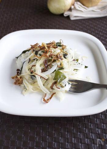 """新玉ねぎを生食で満喫できるサラダです。ポイントは、玉ねぎを薄くスライスしたら、ちょっとだけ""""炒め用""""に取っておくこと。それをごま油で茶色くなるまでとことん炒めたら、生の玉ねぎサラダの上にかけて、完成です♪乾燥わかめを戻したものと一緒に、ヘルシーな一皿を楽しみましょう。"""