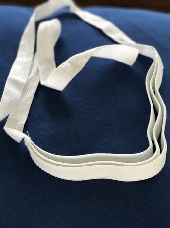 画像のような三重紐(さんじゅうひも)を使います。三本の太いゴムの間に帯を挟んでいきます。この三重紐は一つ持っておくと便利です。インターネットや呉服屋さんでも手に入りますよ。