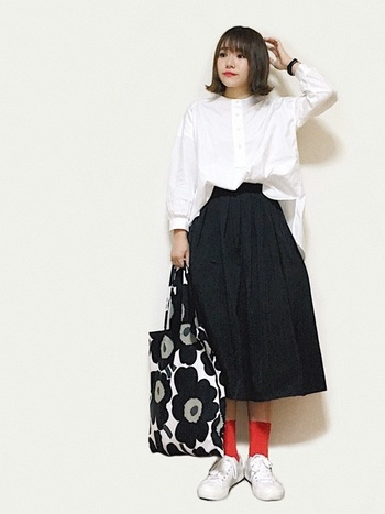 白ブラウスと黒のふんわりスカートのシンプルコーデに、赤ソックスと花柄トートバッグをぴりりときかせて♪ ゆったりめのシャツを合わせることで、やわらかなスカートのシルエットとバランスがとれています。