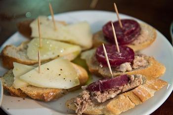 """ピンチョスとは、スペイン語で""""爪楊枝""""や""""串""""といった意味をもち、食材を爪楊枝などで刺してつまんで食べる料理のことをいいます。"""
