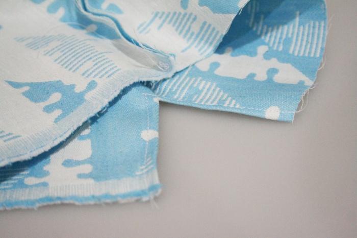 ① 完成した時に両サイドにくる辺の縫い代を、ロックミシンなどで処理しておきます。  ② 内側に表面がくるように生地を半分に折り、両サイドを縫います。このとき、紐通し口部分を、5cmほど縫わずに開けておきます。 ※縫い合わせてある部分と開いている部分の境目を「あき止まり」と言います。お弁当袋など、両側から紐を引いて口を絞るタイプを作る場合は、両端とも「あき止まり」まで縫うようにして下さい。  ③ 縫い代を割ってアイロンをかけます。あき止まり部分は、画像のようにミシンなどでV字に縫って、縫い代を押さえておきます。  ④ 口の部分は、紐が通せるように三つ折りにして縫います。  ⑤ 紐を通して完成です。