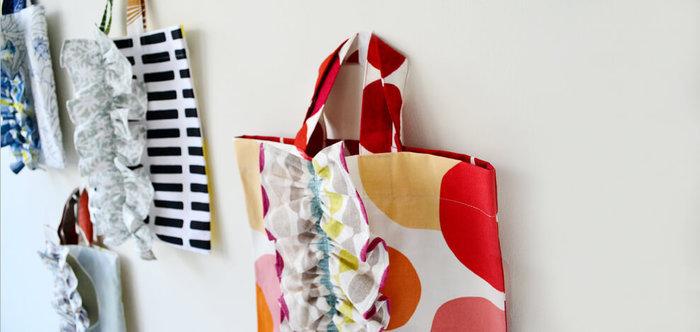 フリルの作り方はとってもシンプルです。 <作り方> ① フリル用の布は、お好みのフリル幅+縫い代で、バッグより長めにカットしておきます。(手でシワを寄せながらバッグにあてると大体の長さの検討がつきます)縫い代を三つ折り端ミシンか、かがり縫いをし、中心にしつけ糸などで並縫いをして絞ってヒダを出します。 ② お好みのヒダが出たら、しつけ糸を玉留めします。フリルをバッグに当てて、まち針でとめるか、しつけをします。 ③ 上から中心をミシンで叩いたらしつけ糸を抜いて完成です。
