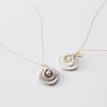 シルクとパールの美しさを融合させた「シェル」シリーズは、凛とした女性らしさを演出する繊細なディテールワークも印象的です。シルク製の貝モチーフで真珠を包む立体的な構造は、職人の高度な技術があるからこそ実現できたもの。金属チェーンのように見えるネックレスのコードパーツも、実はメタリック糸でできているそうです。細部にまでこだわりが詰まった上質なアクセサリーは、身に着けるほど愛着が増し、刺繍ならではの心地よさを感じさせてくれます。