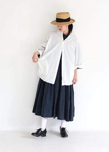黒ワンピースの上に、白シャツをレイヤードした着こなし。モノトーンでまとめたアイテムの中で、ストローハットが季節感溢れるアクセントになっています。白シャツはトップスとしてだけでなく、羽織として活用するのもおしゃれですね。