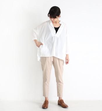 白シャツにベージュのパンツを合わせ、胸元から黒のインナーをちら見せしているコーデ。ゆとりのあるスキッパータイプのシャツは、ちらりとのぞくインナーを変えるだけで、全体の雰囲気をがらりと変えることも可能です。