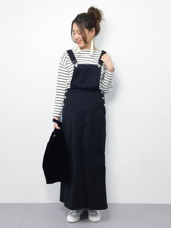 黒のサロペットスカートは、モノトーンでまとめてシンプルに。ボーダートップスと合わせたカジュアルスタイルは、普段使いにもぴったりな着こなしです。
