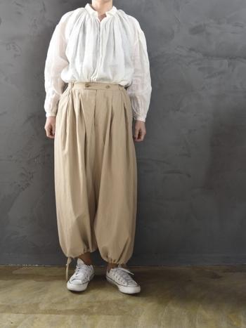 ふわっと膨らんだようなシルエットが、女性らしさを演出してくれる白ブラウス。サルエル風のベージュワイドパンツを合わせて、ちょっぴりユーモア感のある上品な着こなしに仕上げています。