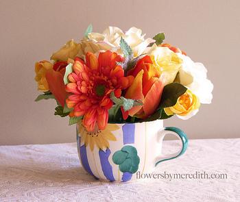 マルチカラーのアレンジに、あえて柄物のカップを合わせることで、温かみがあってにぎやかな雰囲気に。 色数が多くてもサイズが小さいので、うるさい印象になりません。カップの中にオアシス(花の吸水スポンジ)を仕込むことで、こんもり丸い形をキープできます。