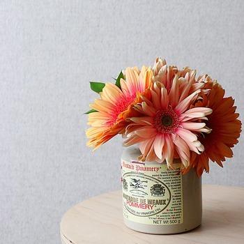 こちらはマスタードの空き瓶にガーベラをぎゅっと束ねて活けたもの。あえてラベルを残してコーディネートするのも素敵ですね。大ぶりな花をあえて短く切って活けるとキュートな雰囲気にまとまります。
