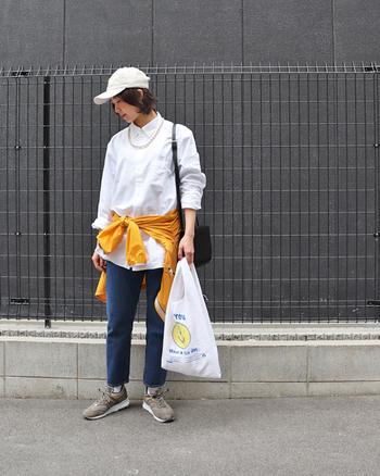 こちらもデニムとスニーカーで白シャツをカジュアルダウン。いちばん上までボタンを留めた白シャツも、キャップをプラスしたり、腰に巻いた差し色のアウターで、ラフな印象の着こなしにしてくれます。