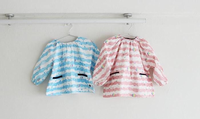 袋物が完成したら、スモックにも挑戦してみませんか? ボタン開きなどがあるものよりも、ネックラインにゴムを入れたかぶるタイプのほうが、縫製もお着替えも簡単です。  写真のように袖と身頃が一枚の布で繋がっているものや、それぞれのパターンが分かれているものがあります。  薄手で半袖の「夏用スモック」と、肌寒い時にはさっと被れて便利な、長袖の「冬用スモック」の二枚があるとより快適ですよ。