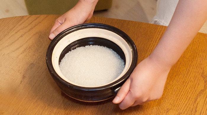 お米は、炊く前に研いで、水につけておきます。夏は30分、冬は1時間が目安。 お米が水を吸ったら、ざるにあけてよく水気を切り、土鍋に移して水を入れます。水は1合につき200ccが目安。好みに合わせて調節してみて。