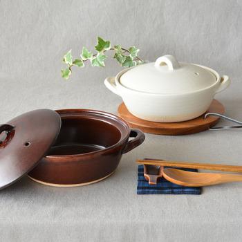 """鍋料理やご飯を炊くだけでなく、色々な用途で使いたい土鍋。手作業にこだわった温かみのある陶器店・スタジオMの土鍋は、平な底で深すぎない使いやすさが魅力です。色は、どんな食卓にも合わせやすいマットな白と、こっくりとしたあめ色の2色。土鍋ご飯の大きな魅力である""""おこげ""""がたっぷりできるのも嬉しいポイントです。"""
