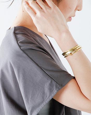 メイドインU.S.Aかつハンドメイドにこだわり、アナログな手法から生まれる丸みのあるラインが特徴のシンプルなバングルです。素材には真鍮を使用しており、着用していくにアンティークのような雰囲気に変化していきます。