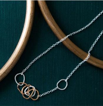 小さな輪が連なり、複雑なディテールを描いた繊細なネックレスです。ゴールドの部分には、洗練されたシャンパンゴールドのような色味となり落ち着いた印象と艶で首元を着飾ってくれます。