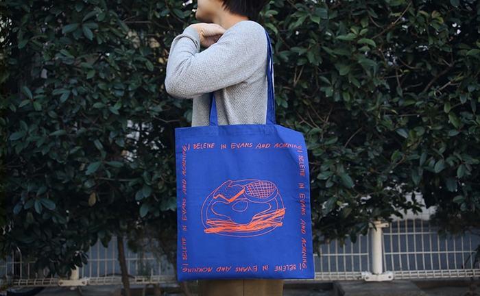 """ペインターnorahiさんの作品をプリントした「Morning UKABU Bag」は、ジャズピアニストのビル・エヴァンス氏による楽曲""""You Must Believe In Spring""""をオマージュして作られたトートバッグです。"""