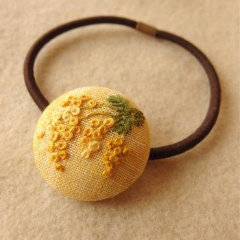 丸い形が可愛いくるみボタンのヘアゴムに、ミモザの花を咲かせた作品です。くるみボタンを作るときは、キルト芯をはさみこんでぷっくりと仕上げるのがコツです。材料は100円ショップで購入できるので、ぜひチャレンジしてみましょう♪