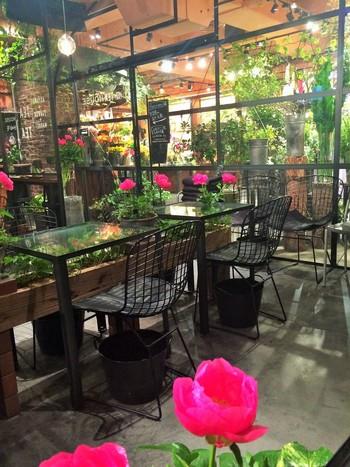 """Living With Flowers Every Dayの体感""がコンセプトで、たくさんのお花やグリーンに囲まれたカフェ。大きなガラスがまるで温室のよう。"