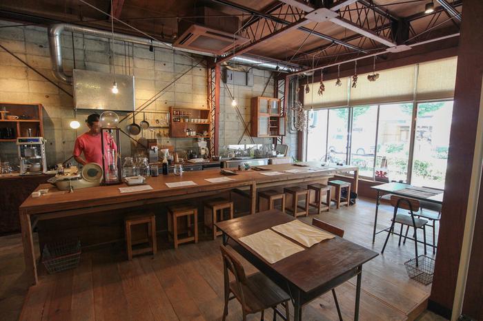 車のパーツ会社だったところをリノベーションした自家焙煎珈琲のお店。天井の鉄骨やコンクリートブロックの壁、ザクッとした男前なインテリアに、大きな木のカウンターや椅子を配し落ち着ける空間を創り出しています。