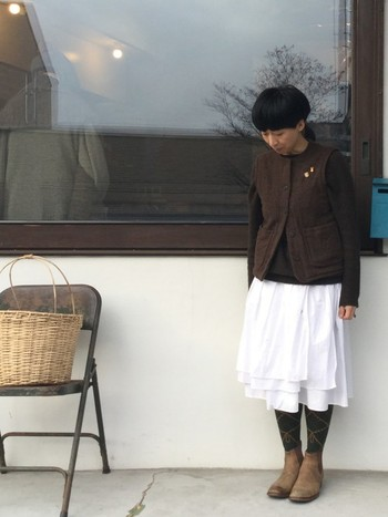 ガーリーな白い膝丈スカートですが、ダーク系のトップスと柄タイツを組み合わせると、ちょっと大人の雰囲気に。白さが際立つ、絶妙な色使いが素敵です。寒さが残る春先は、長めのアウターを重ねても◎