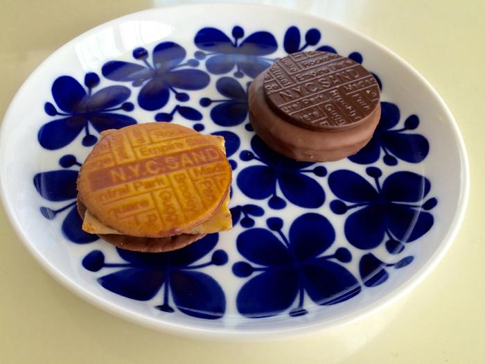 """手前の「N.Y.キャラメルサンド」は、1960年代のニューヨークで作られていたハバナサンドを基に開発されたクッキー。サクサクのチョコレートクッキーの中に、なめらかな舌触りのキャラメルをサンドしたこだわりの味。トロトロのキャラメルはクッキー、チョコレートとともに口の中でほぐれながら、とろけて消えていきます。  「N.Y.リッチスカッチサンド」は、バタークッキーに古くからヨーロッパに伝わる飴を高温で煮詰めて作る""""スカッチ""""をサンド。スカッチは、アメリカで幅広い世代に親しまれ、家庭の味でもあるんですよ。さらに、ビターなダークチョコレートと香り豊かなミルクチョコレートを絡めて、全部で8層に仕上げた贅沢な味。  どちらも食べてみたくなりませんか?"""