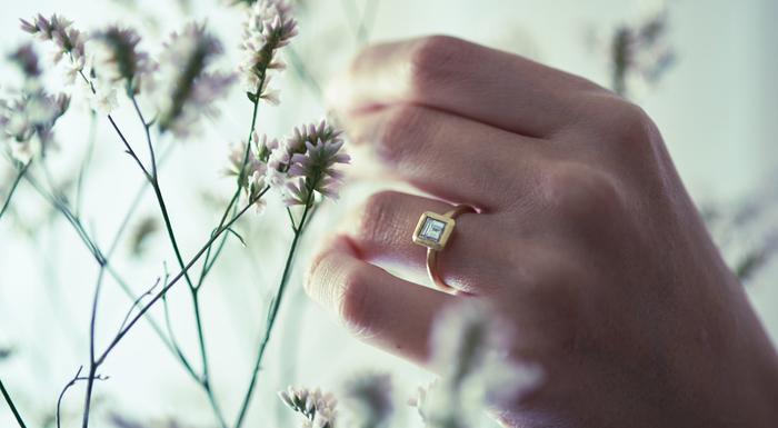 額に見立てたフレームの中にダイヤモンドを配した、上品なデザインのエンゲージシリーズ【額 GAKU】。東京彫金の職人が丹念に作りあげるエンゲージリングは、シンプルな美しさと凛とした存在感が特徴的。こちらの写真の四角いフレームの「SQUARE(スクエア)」と、丸いフレームの「CIRCLE(サークル)」の2種類のデザインを展開しています。