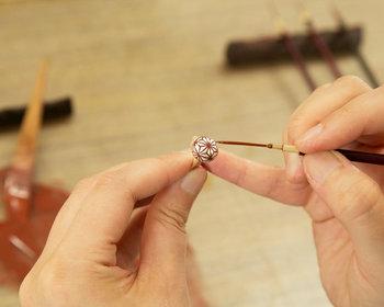 「蒔絵」とは日本に古くから伝わる漆工芸技法のひとつ。漆器の表面に漆で絵や文様などを描き、乾かないうちに金粉などの金属粉を「蒔いて」定着させる技法です。蒔絵の技法を用いて精緻な和柄を描いたこちらのパールネックレスは、職人の細やかな手仕事と日本の伝統美を感じることのできる逸品です。