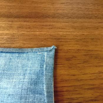 画像のように、地縫いのミシンの線がギリギリ見えるか、生地が少し厚めの場合は1ミリほど内側になるラインで、縫い代を後ろ側に折り、アイロンでしっかりと押さえます。  縫い代の角を指の先で押さえたまま、アイロンでつけた折り目を崩さないようにするイメージで、表に返します。  表に返したら、表から目打ちやまち針を使って形を整えたら完成です。目打ちで引っ張りすぎると歪んでしまうので注意! 引っ張りすぎたら、また裏に戻して縫い代を折るところからやり直してくださいね。