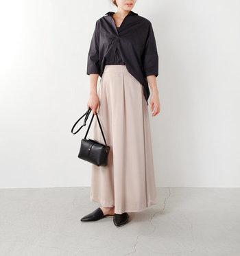 くすみピンクのロングスカートに、黒のブラウスを合わせたレディライクなコーディネート。足元やバッグも黒で合わせて、シンプルかつ上品な着こなしに。明るすぎるピンクは黒と合わせると浮いてしまうので、シックな印象のピンクを選ぶようにしましょう。