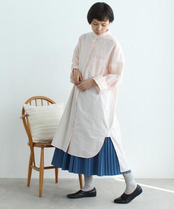 サイドにスリットが入った、薄ピンクのシャツワンピース。ワイドシルエットなシャツワンピは一枚で着ると少しぼんやりした印象になってしまうので、引き締めカラーのロングスカートを合わせて、着痩せ効果もプラス。ワンピース×スカートのレイヤードで、おしゃれ上級者の雰囲気に♪