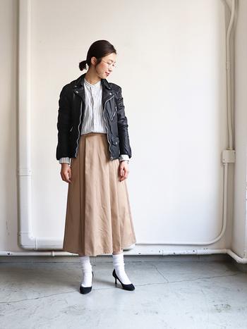 メンズライクなレザージャケットに、ベージュのロングスカートを合わせたコーデ。トップスにはストライプのシャツをインして、アウターのハードさを和らげています。ヒールパンプスや白ソックスも女性らしいアイテムで、大人カジュアルなスタイリングの完成です。