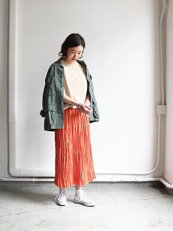 オレンジのロングスカートに白トップスを合わせ、肩からカーキのライトアウターを羽織ったスタイル。オレンジ×カーキの組み合わせが、華やかさはしっかりあるのに落ち着いた印象◎ 大人女子の春のお出かけにぴったりなスタイリングですね。